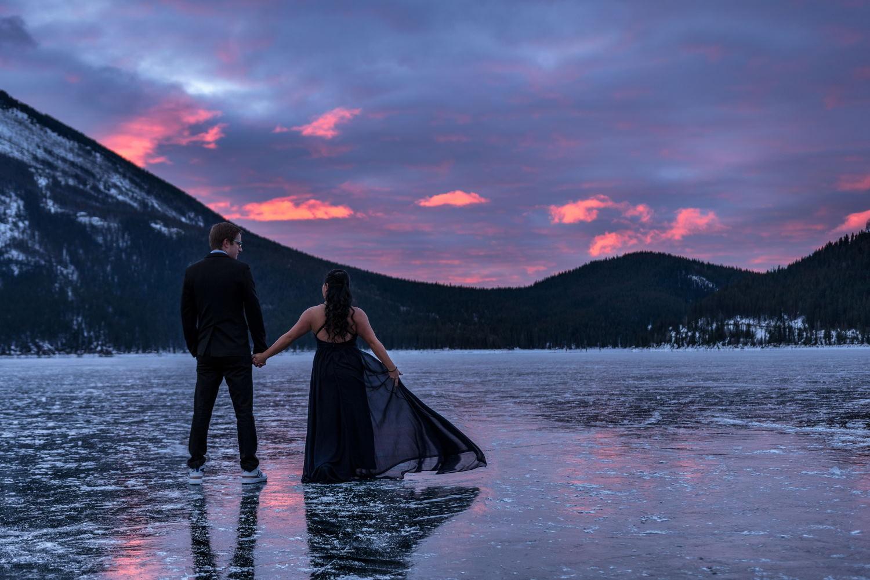 engaged couple on the frozen Minnewanka Lake during sunrise